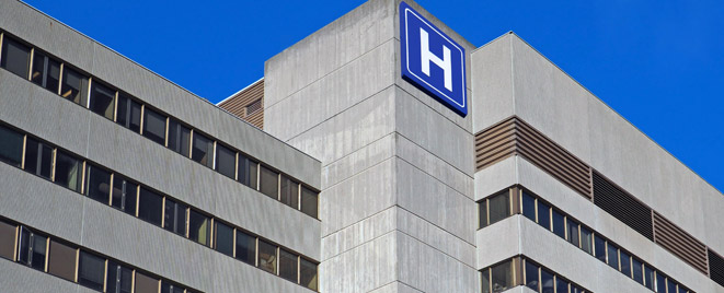 Large concrete building with H sign for hospital stock photo